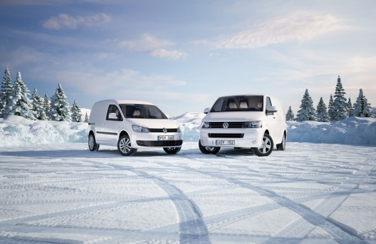 Volkswagen trasporter and Caddy at a parkingplace in the winter, at sunset and midnight frozen cars with frost and ski tracks and path. Vinter bilar snö